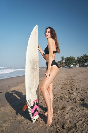 Female model with long hear style and beach wear with surfboard at sunny morning at the Balinese ocean beach