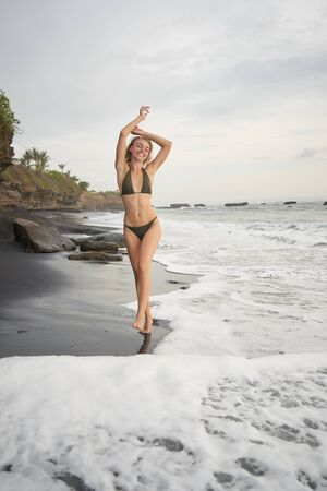 Black sand beach and young woman running in enjoy nature