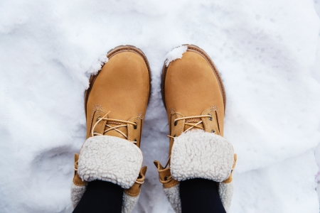 Pair brown boots in white fresh snow photo