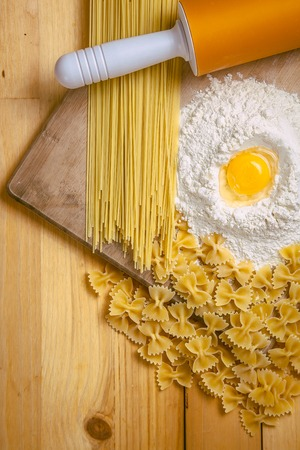 Pasta and yolk in flour on the wooden table photo