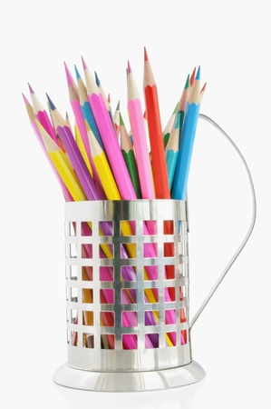 Colored pencils in cup holders against white background