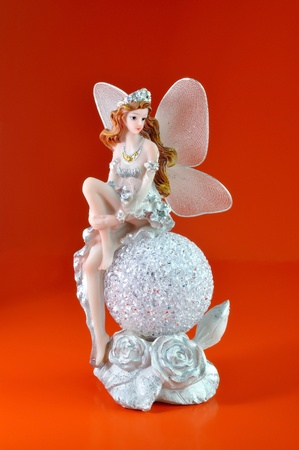 Fairy on the ball figurine on a red background