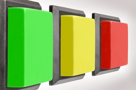 Three electrical switch with colored buttons against white background