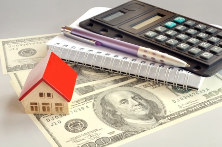 Pocket calculator, notepad, pen and a small house on a hundred dollar bill Stock Photo - 9733988