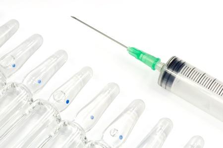ilness: Single use syringe and vaccine against white background