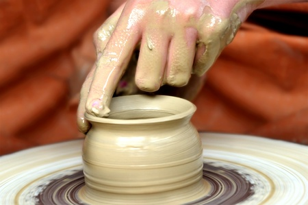 Clay pot on the wheel and two hands  photo