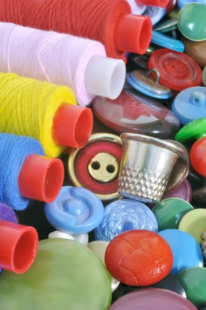 Spools of colored thread and a thimble on the buttons