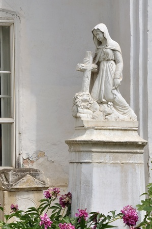 An ancient statue of a grieving woman leaning in the cross