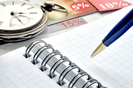 Old clock, notebook, coupons and a blue pen Stock Photo - 12065702