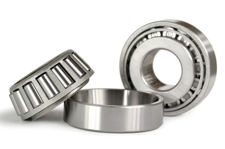 Two roller bearings on a white background. Focus on the first bearing