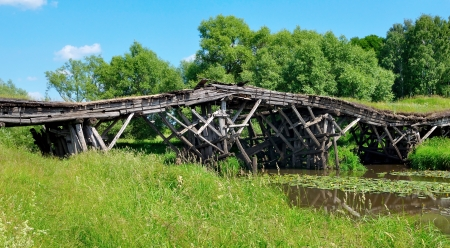 Old ruined wooden bridge over a small river Stock Photo