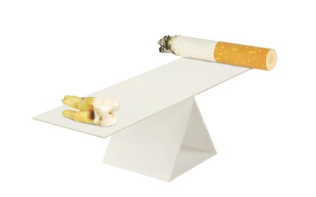 implication: Cigarette and aching tooth on the scales on a white background