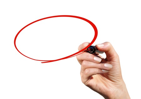 The hand with the marker draws a red ellipse on the transparent screen Stock Photo