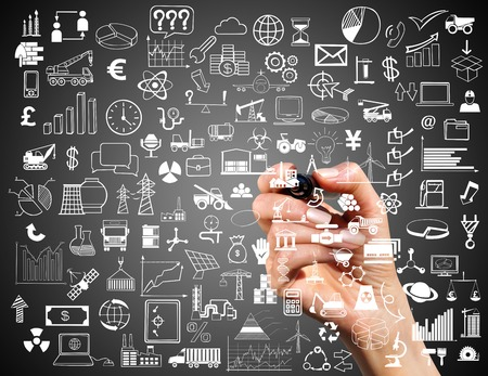Collage of business symbols and marker in hand on a dark background Stock Photo