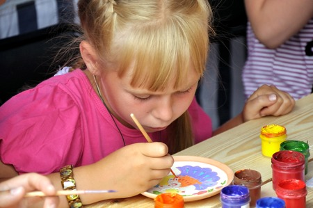 Krapivna, RUSSIA -18 June: unknown girl draws paints on a saucer on the traditional annual Festival of Nettles June 18, 2011 in Krapivna, Tula, Russia.