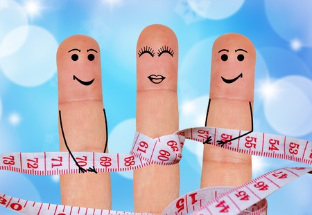 criterion: The concept of a healthy lifestyle. Three fingers with painted faces measure waist
