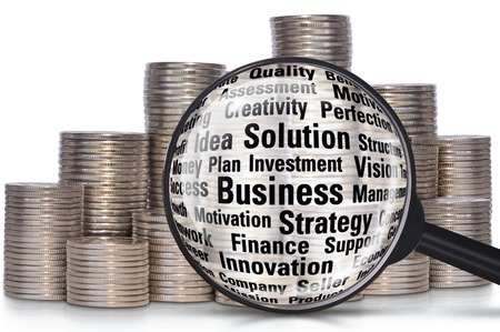 capitalization: Coins and magnifier on a white background. Collage on the theme of finance and business