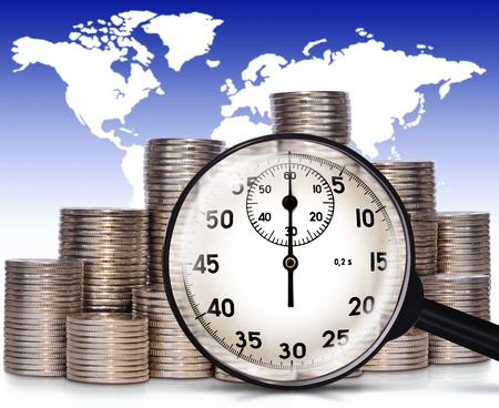 capitalization: Coins and magnifier on a background map of the world. Collage on the theme of finance and business