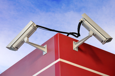 Two video cameras mounted on the wall on brackets Stock Photo