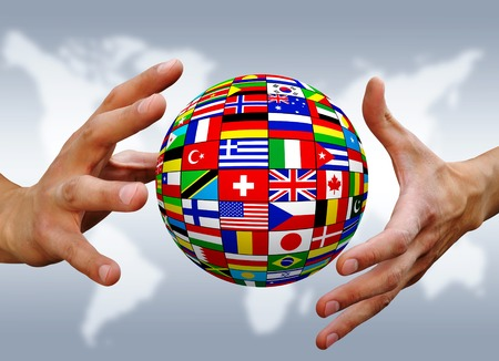 Ball of national flags between the hands on blurry gray background