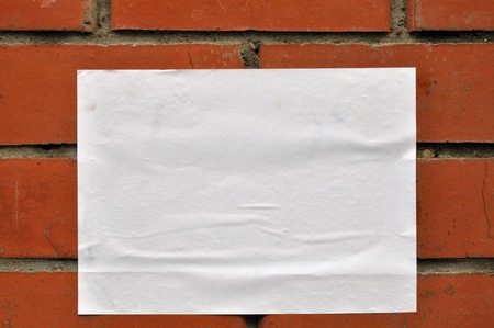 A sheet of clean white paper on the wall from red brick Imagens