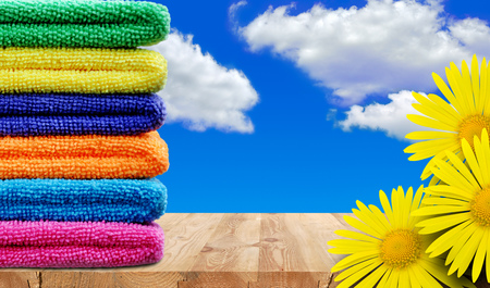 Stack of colored towels and yellow flowers on a wooden shelf against the sky Stock Photo