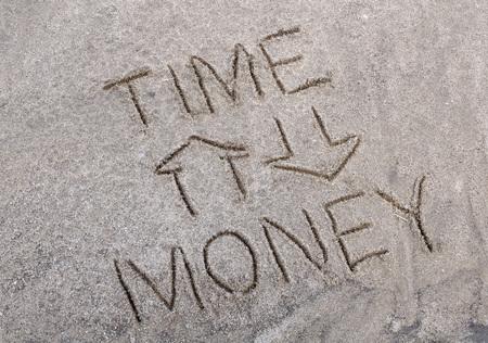 suelo arenoso: dependencia esquem�tica de tiempo y dinero dibujado en el suelo arenoso Foto de archivo