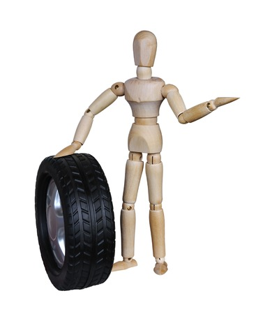 Wooden mannequin holding a car wheel on white background