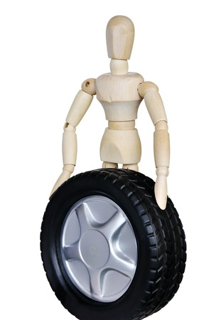 Wooden mannequin holds in front of a car wheel on white background Stock Photo