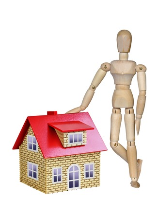 Wooden mannequin and a house with a red roof on a white background Stock Photo