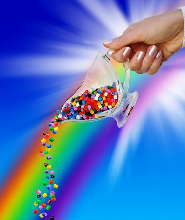 Hand with colored beads in the gravy boat against the sky and rainbows Stock Photo