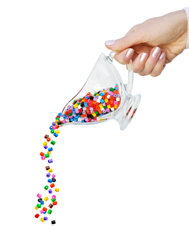 Colored plastic beads spilling from glass dish in a female hand on a white background