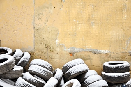 A pile of old tires near a dilapidated wall in the background