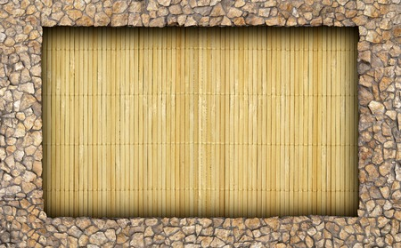 Mat made of bamboo in the wall of natural stone as background Stock Photo