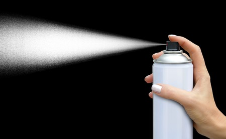 The dispersion jet from an aerosol can in feminine hand on dark background Stock Photo