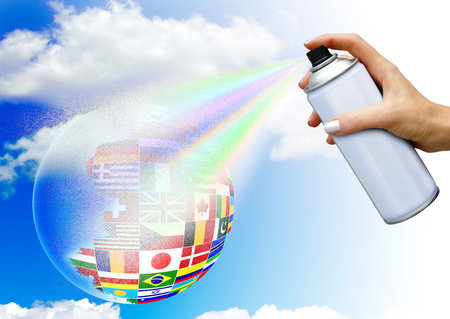 Hand with aerosol spray paints ball in the colors of national flags on sky background. The concept of world community Stock Photo