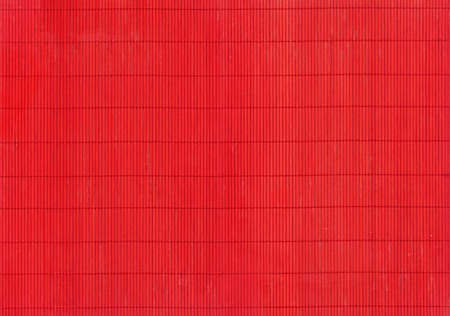 splinter: A fragment of the red mat of interwoven chips of bamboo as background Stock Photo