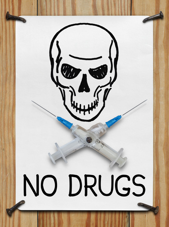Banner with a skull and needles nailed to a wooden wall. The concept of drug addiction Stock Photo