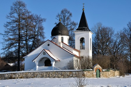 Small rural orthodox church behind a stone wall in winter day
