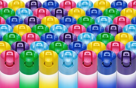 Aerosol cans with colored plastic caps on the injectors