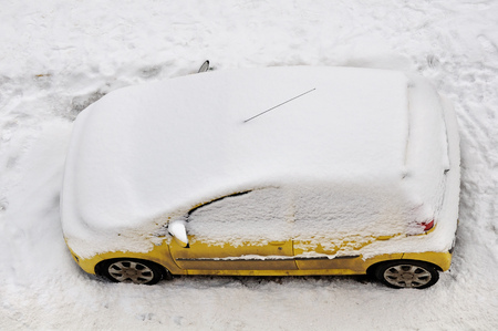 The yellow car in the parking lot covered with snow