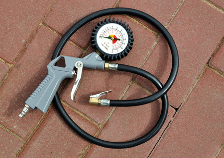 Air gun with pressure gauge and connecting hose for pumping tires on the background paving slabs Stock Photo