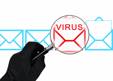 The concept of computer security. Hand with magnifying glass scans the email