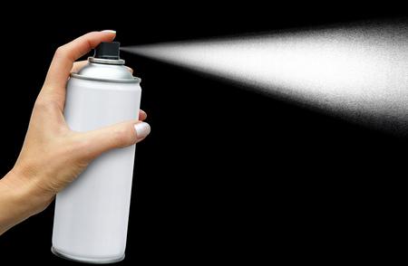 The dispersion jet from an aerosol can in feminine hand on dark background Reklamní fotografie