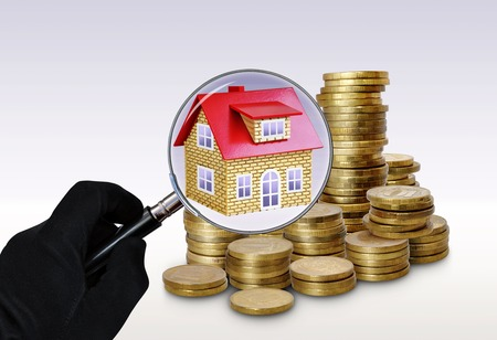 A house with a red roof in the background stacks of coins. The concept of real estate and finance