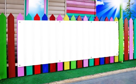 A white banner mounted on a wooden fence painted with paints of different colors