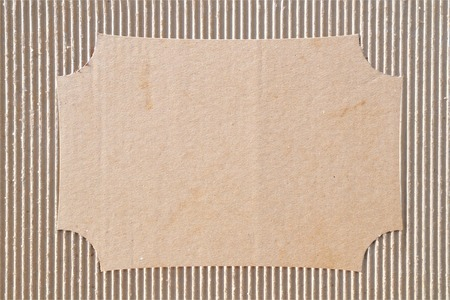 Fragment of corrugated cardboard with a cut out area for text or drawing.