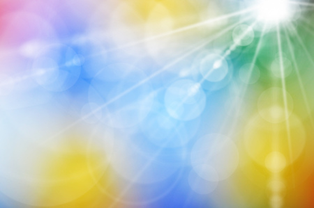 Rays and highlights from a bright light source on a blurred abstract color background.