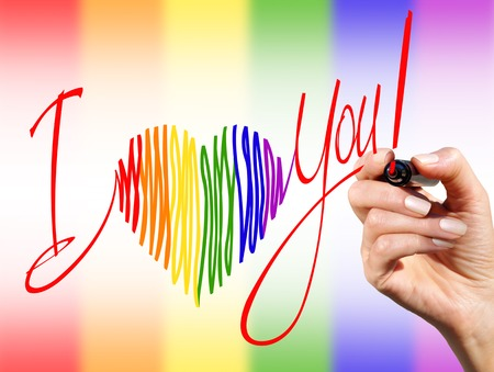 Rainbow heart in a declaration of love and a hand with a marker on a blurred color  background Stock Photo