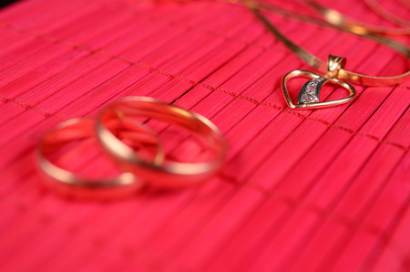 constancy: Two gold wedding rings and gold heart with chain on the red bamboo surface